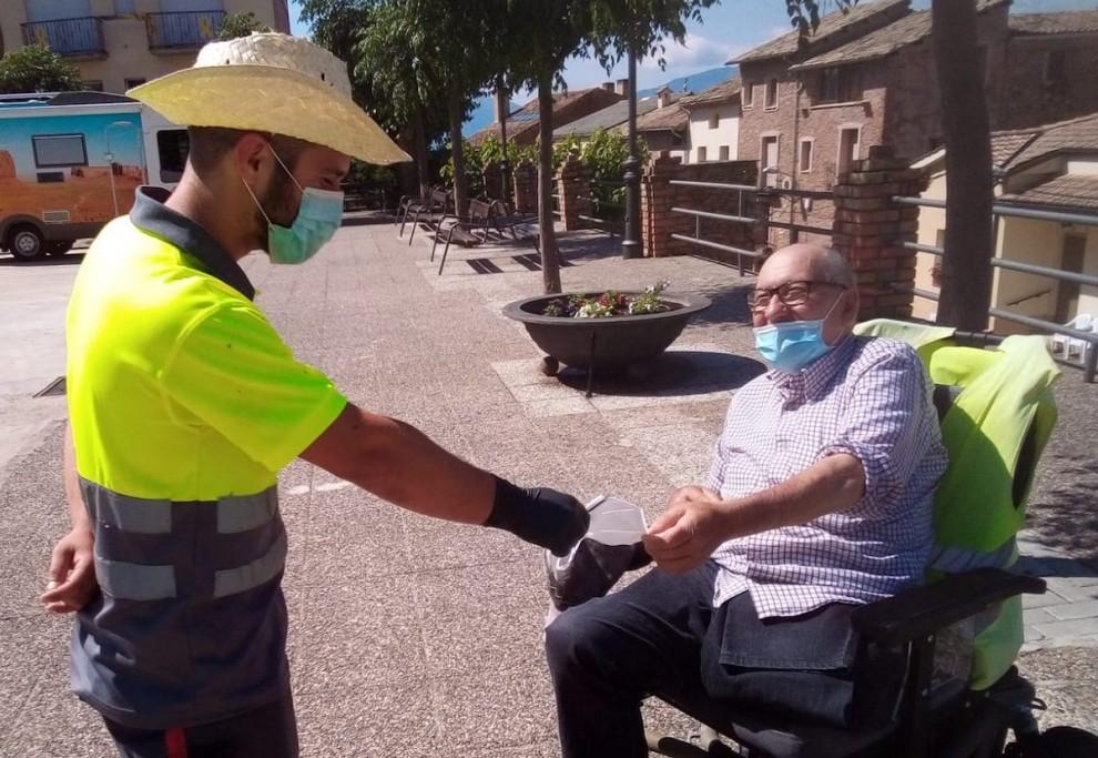 Un treballador de l'ajuntament repartint una mascareta a un veí del poble