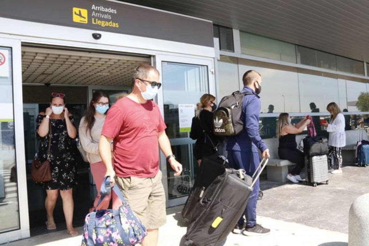 Turistes amb maletes, a la terminal d'arribades de l'aeroport de Reus, en el primer avió que aterra a la capital del Baix Camp des de l'alarma
