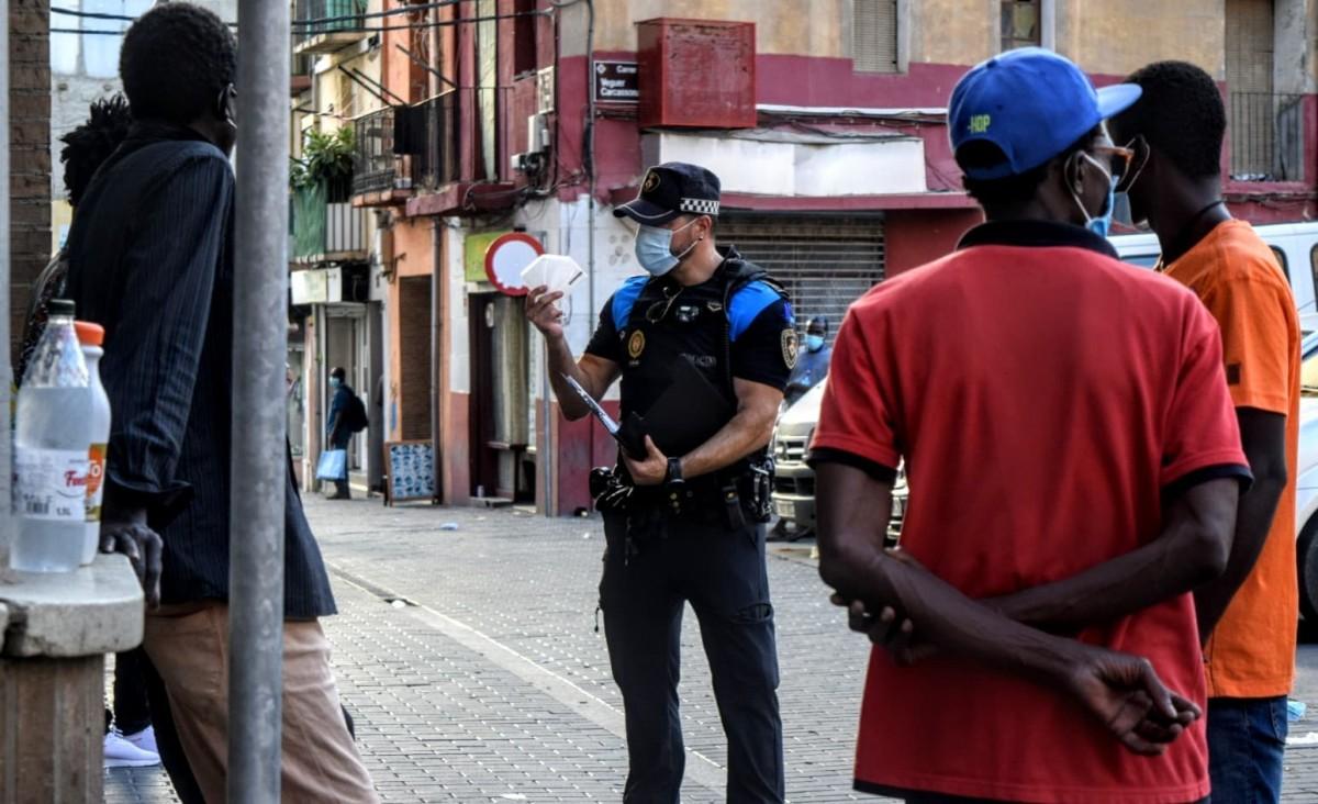 Un policia ensenyant una mascareta a un grup d'immigrants a Lleida