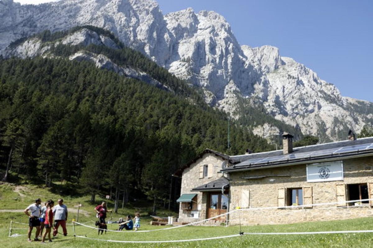 Zona del refugi Lluís Estasen, amb excursionistes i el Pedraforca darrera.