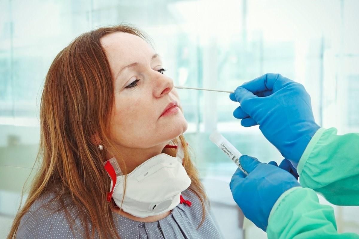 Una dona fent-se un test PCR de coronavirus.