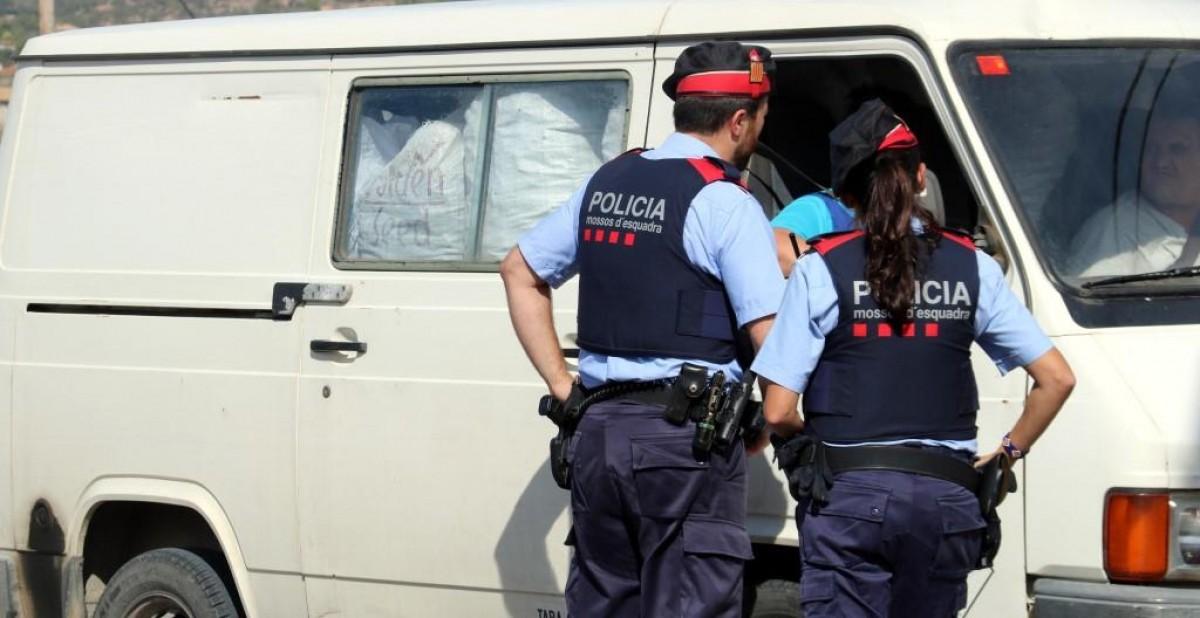 Dos mossos d'esquadra fent preguntes a un conductor