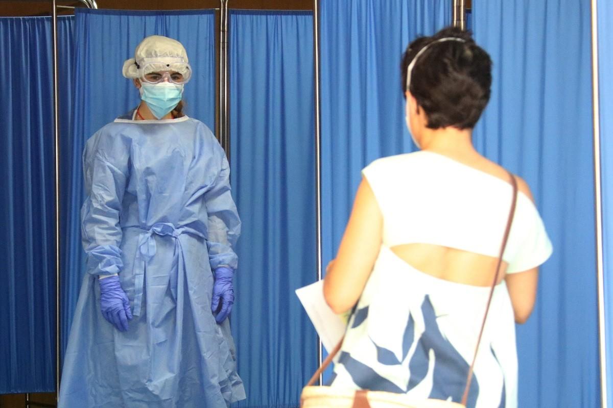 Una sanitària rebent una dona que va a fer-se una PCR.