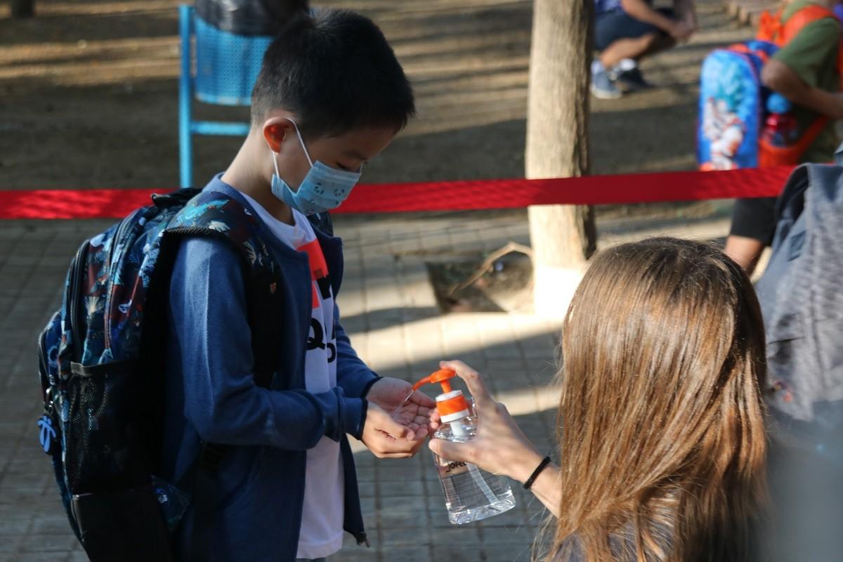 Un alumne rentant-se les mans amb gel hidroalcohòlic abans d'entrar a classe