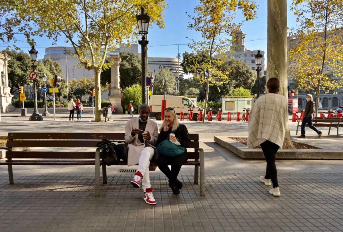 Ciutadans prenent un cafè en un banc de Barcelona