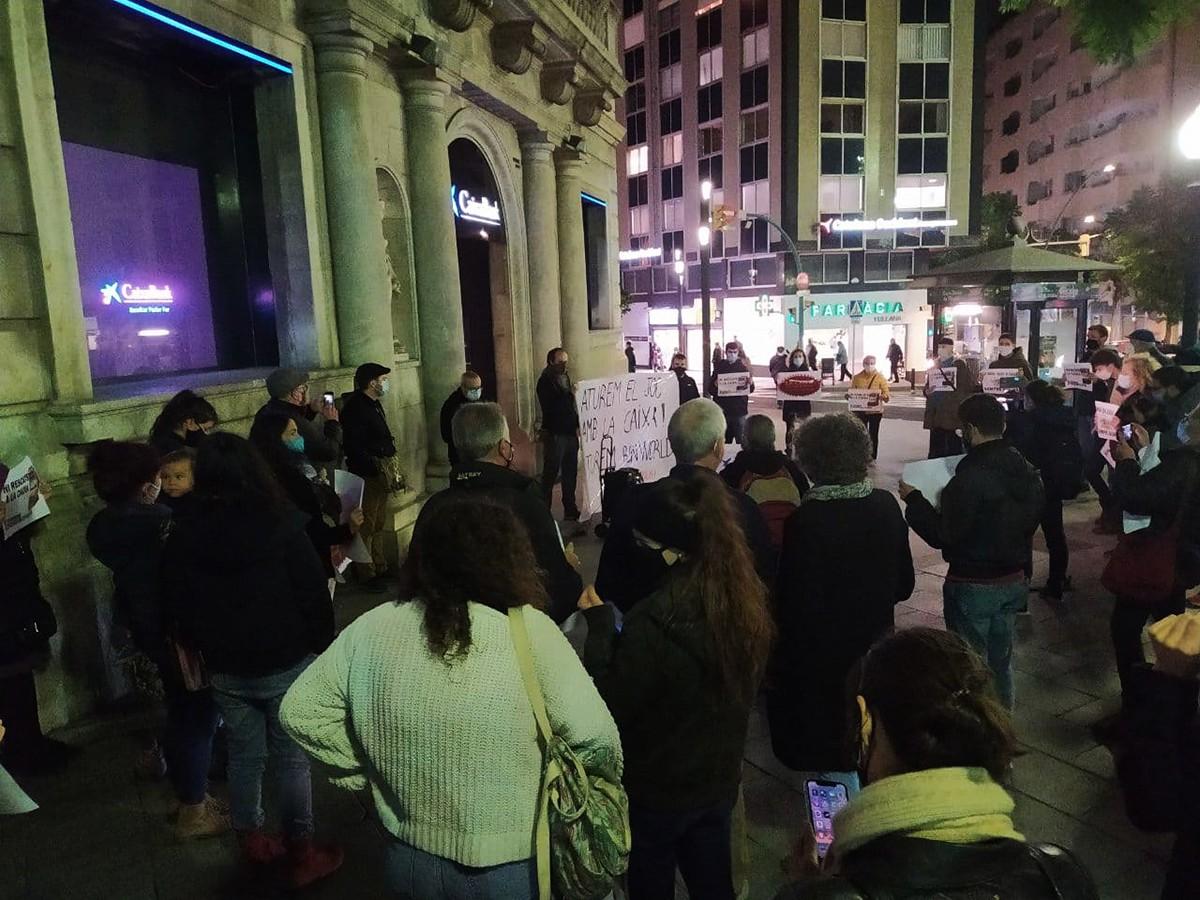 Mig centenar de persones han protestat aquest dijous al vespre davant la seu de La Caixa a la Rambla Nova de Tarragona.