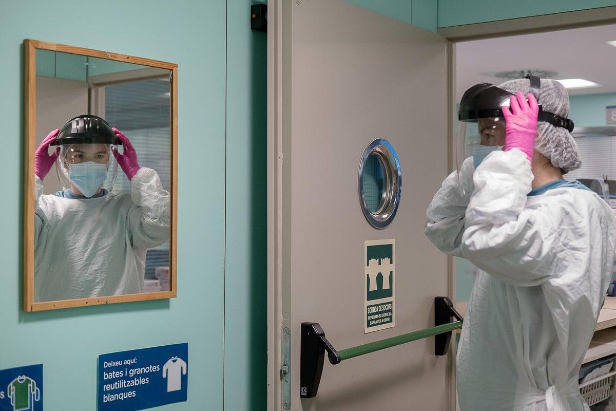 L''Àngels Batle posant-se l'EPI, a la UCI de l'Hospital Universitari de Vic