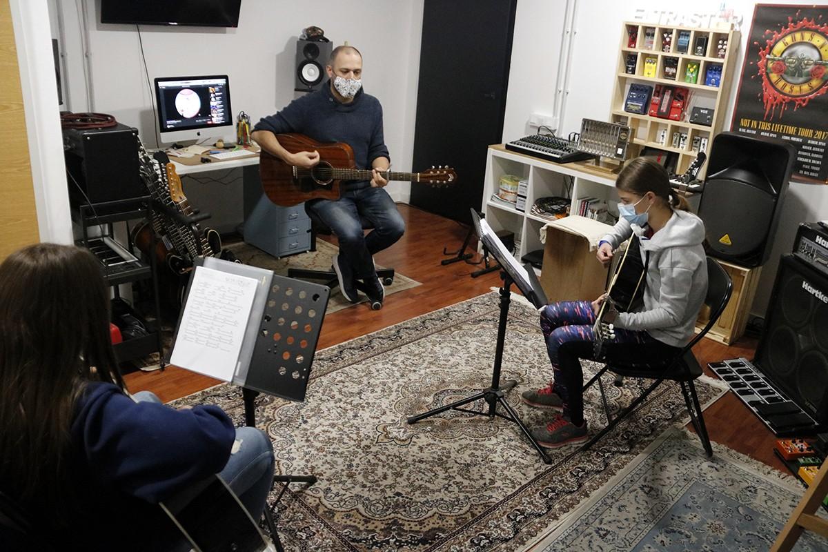 Un professor fent classes de guitarra