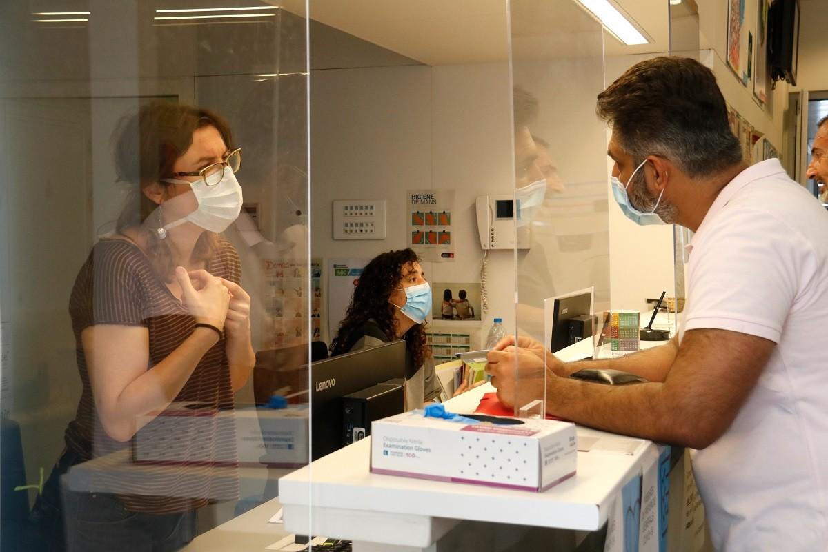 Una treballadora atén un usuari en un centre de serveis socials