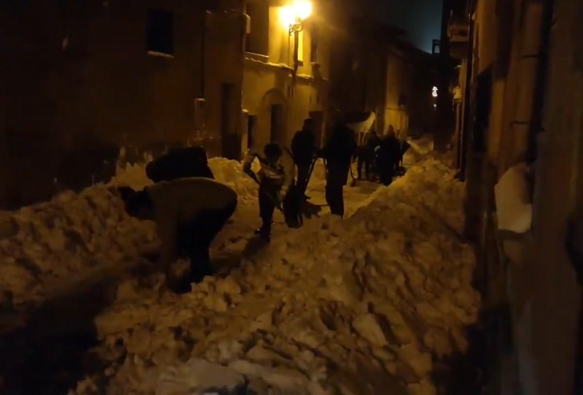 Diversos veïns de Vilanova de Prades, ahir al vespre, enretirant la neu amb pales.