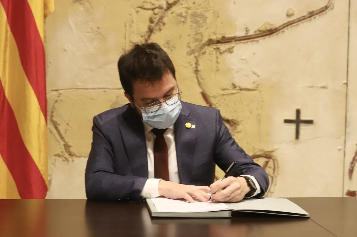 Pere Aragonès signant el decret d'ajornament de les eleccions