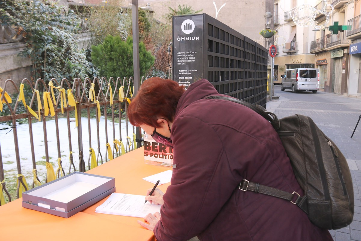 Una olotina signa a favor de l'amnistia en l'exposició d'Òmnium davant l'església de Sant Esteve.