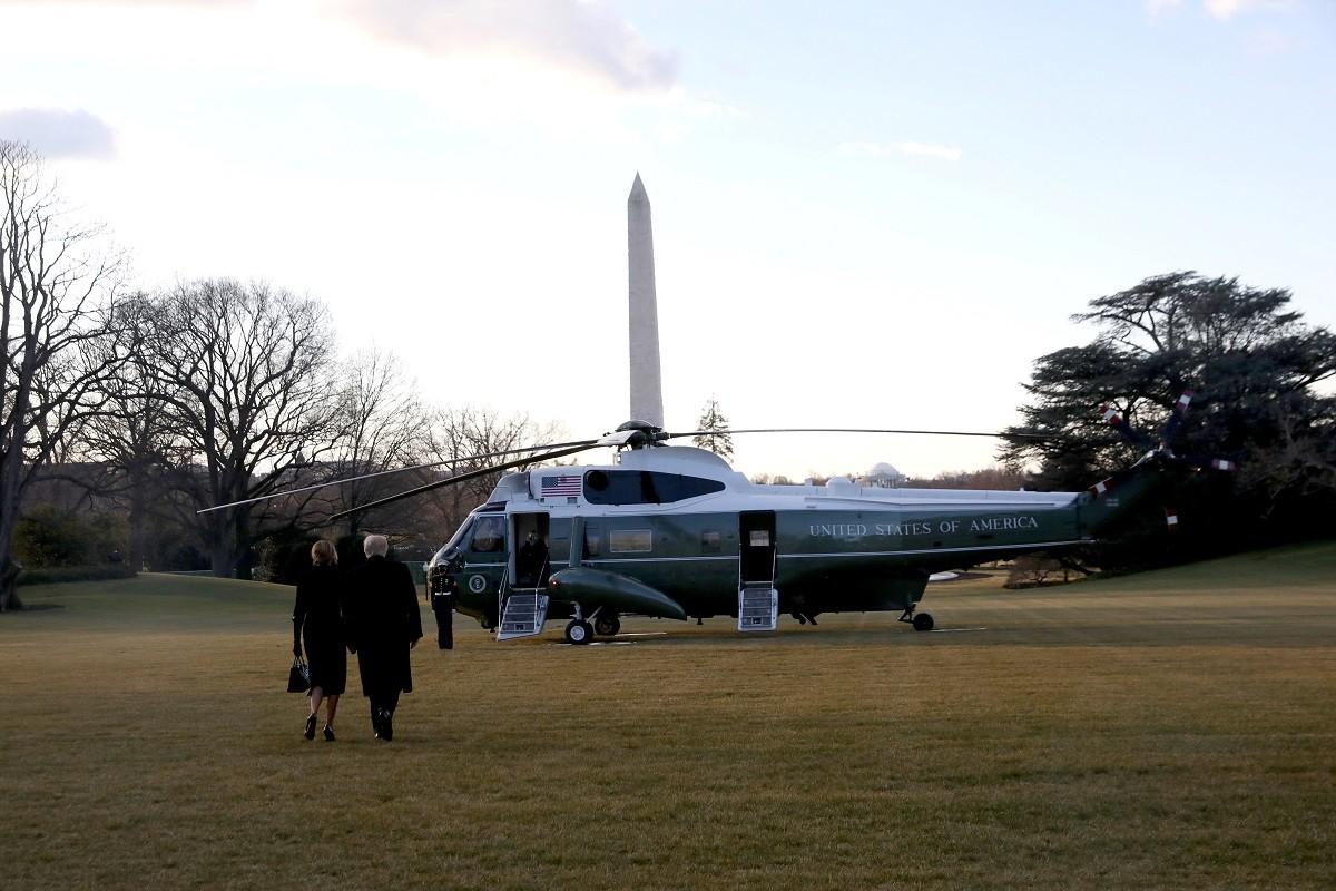 Els Trump, d'esquena, dirigint-se a l'helicòpter