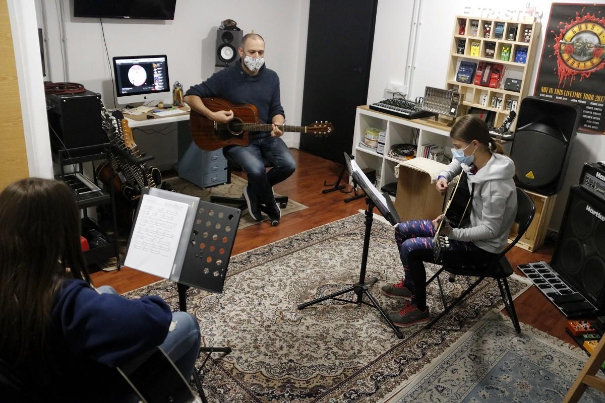 Un professor de guitarra amb els seus alumnes