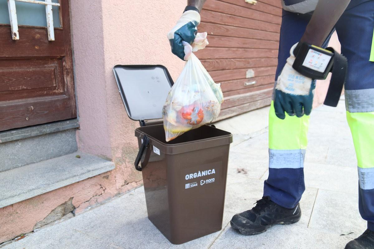 Un operari traient una bossa d'escombraries del cubell de la fracció orgànica.