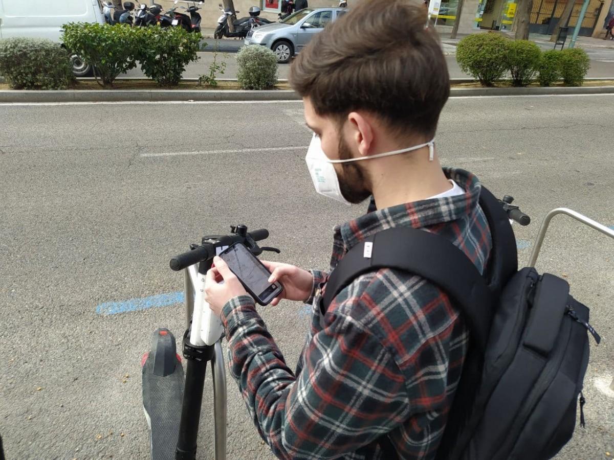 Un usuari, utilitzant l'aplicació d'un patinet elèctric.