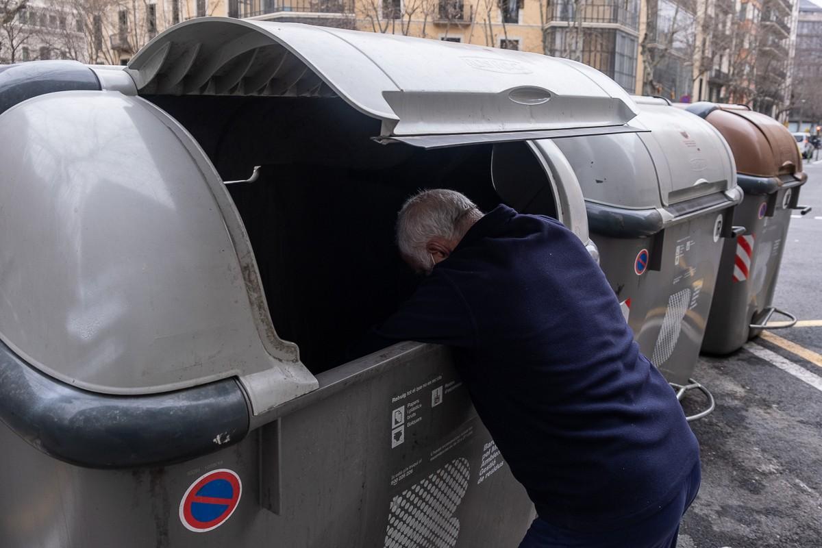 Un home buscant a l'interior d'un contenidor.