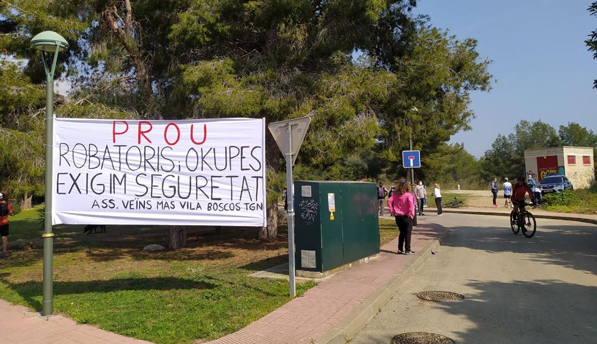 Una pancarta presidia l'acte de protesta al carrer del Falciot, de la urbanització de Boscos.