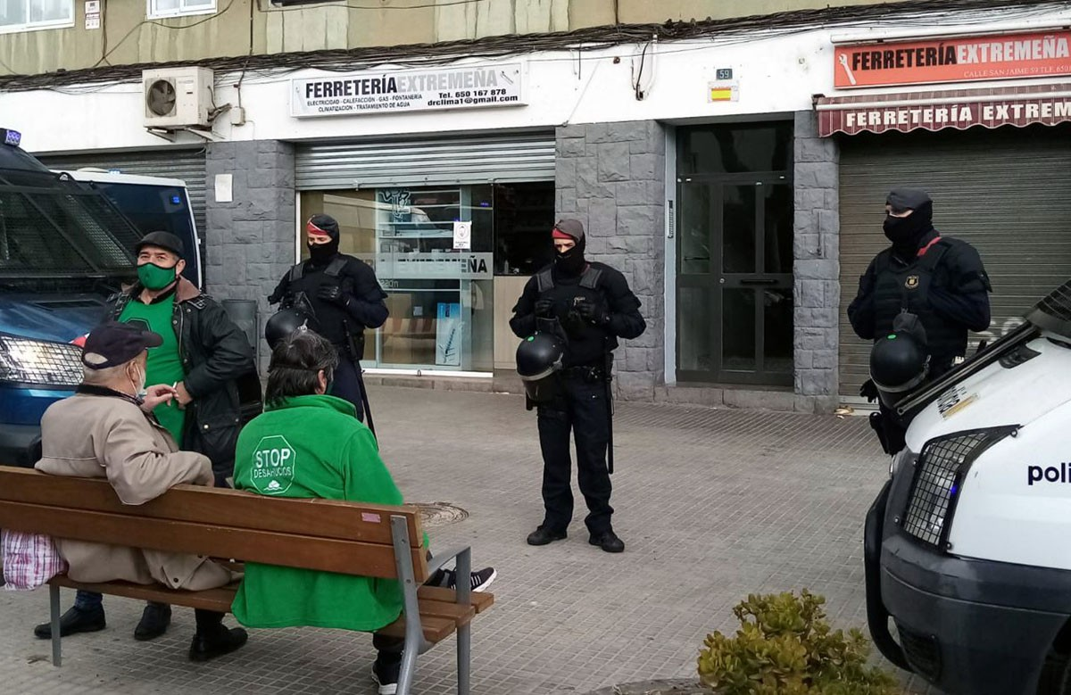 Agents dels Mossos a la porta de l'edifici amb membres de la PAH