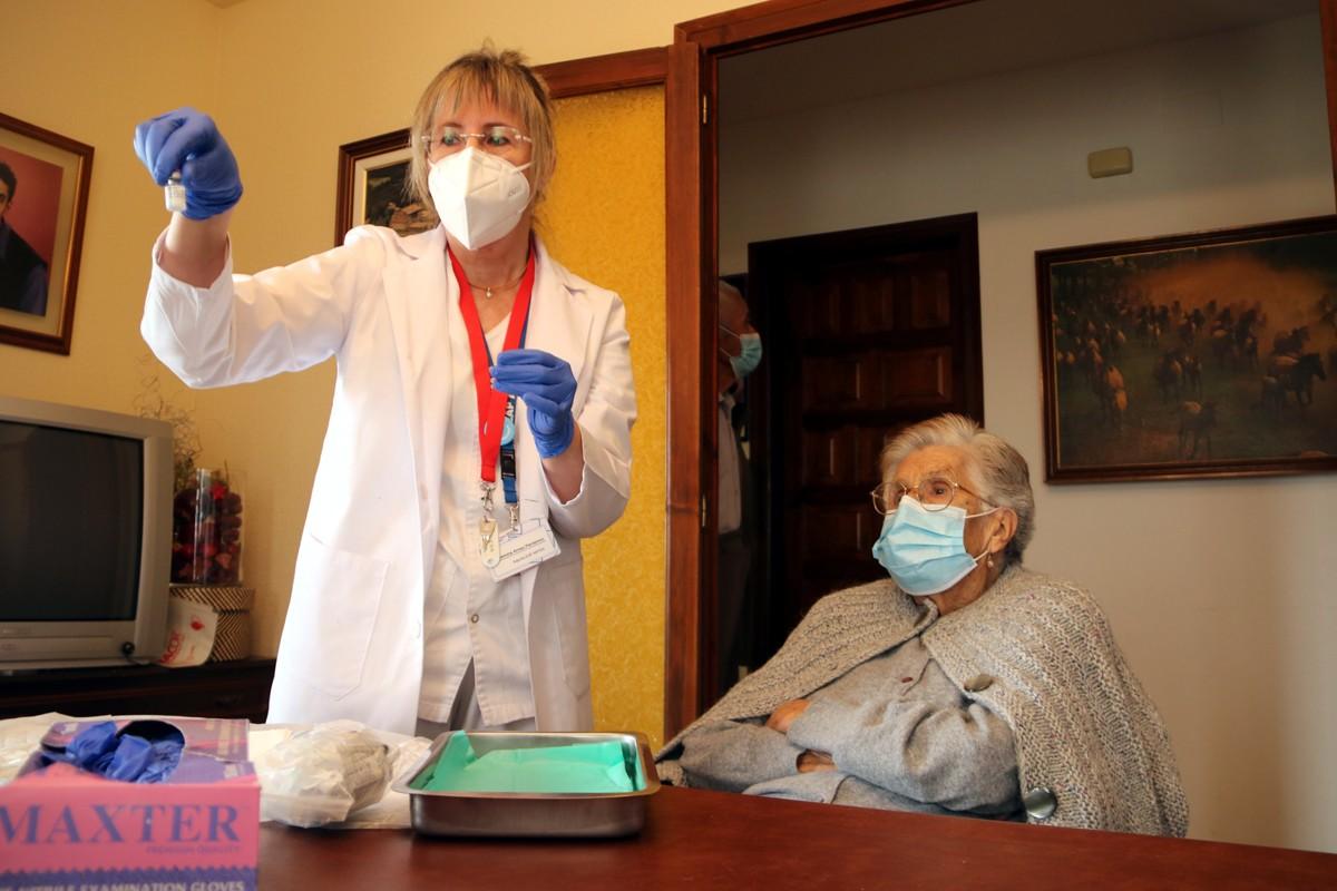 La Concepció Capdevila i la infermera a punt de vacunar-la al menjador de casa seva
