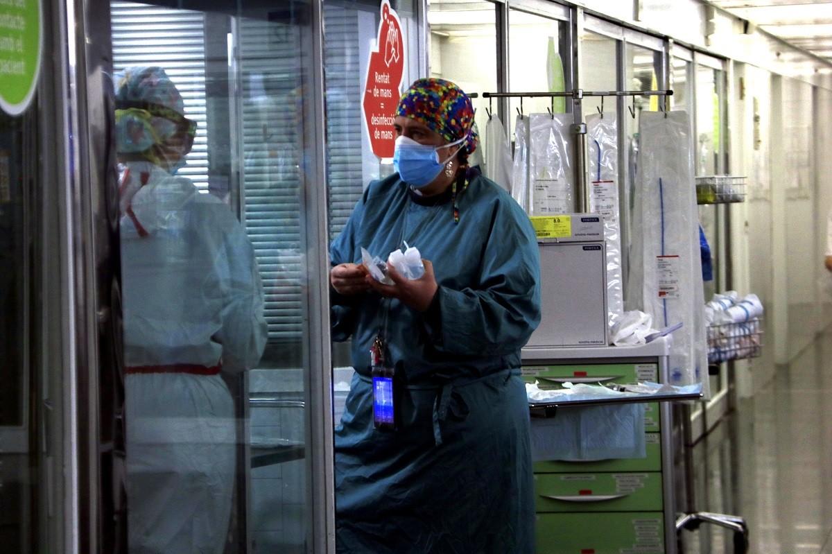 Sanitària portant material a una companya en una UCI.