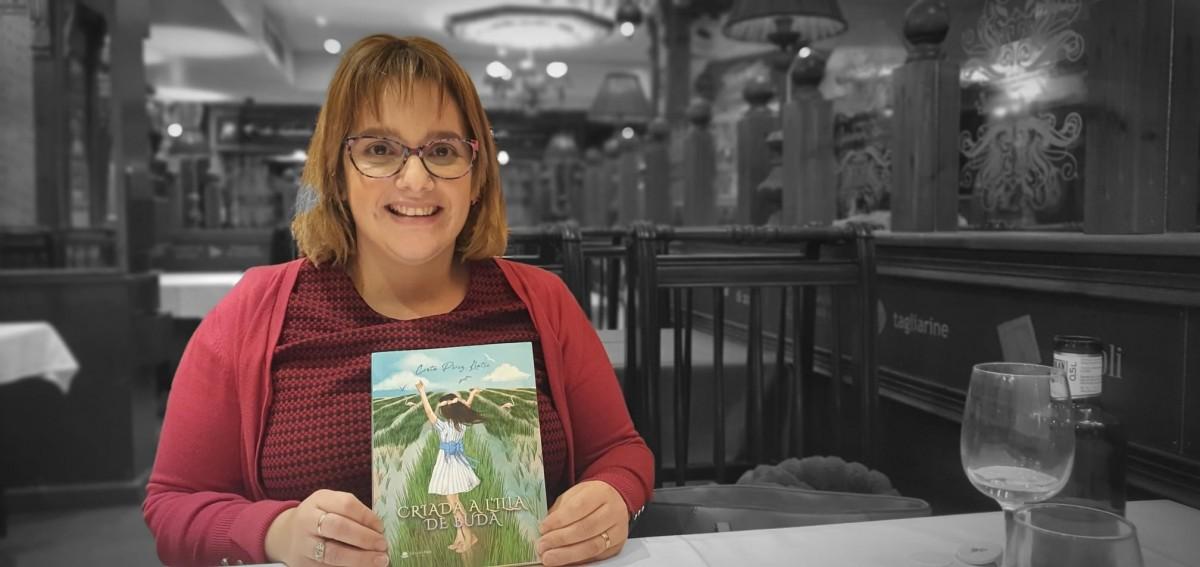 La periodista Cinta Pérez Llatse amb un exemplar del llibre 'Criada a Buda'