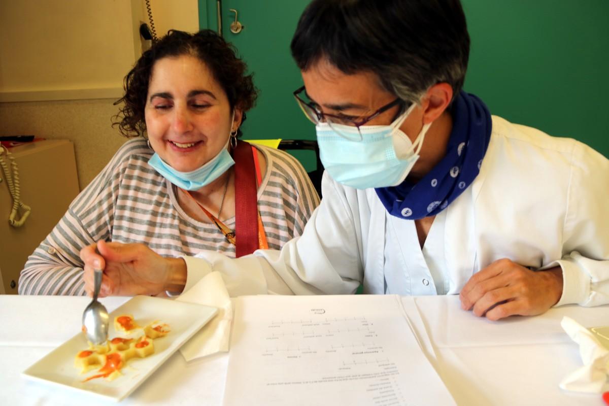 Una de les usuàries del centre de disminuïts físics de Manresa tasta un plat cuinat a partir de la tecnologia 3D