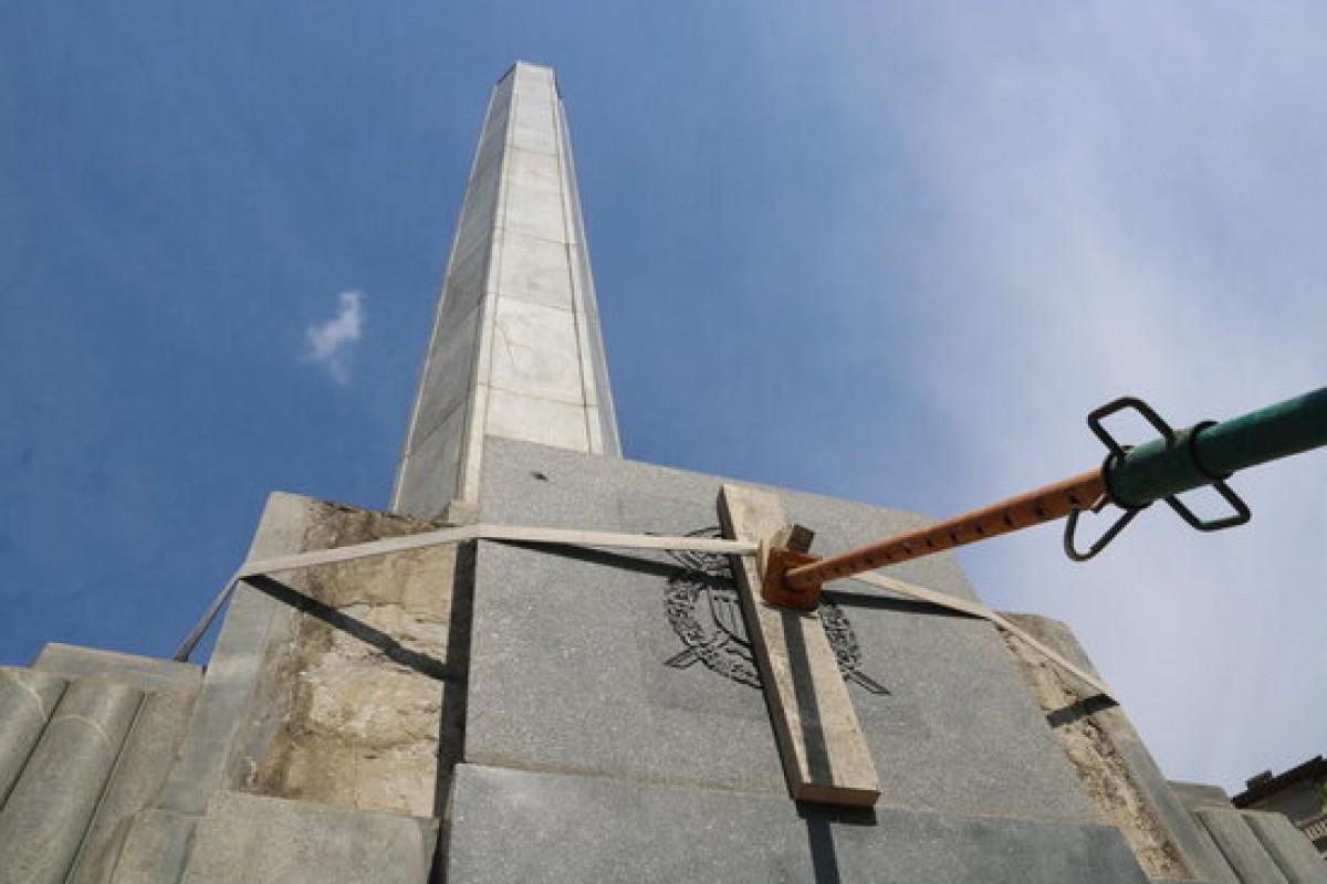 La placa situada a la base de l'obelisc subjectada per una barra poc abans de ser retirada