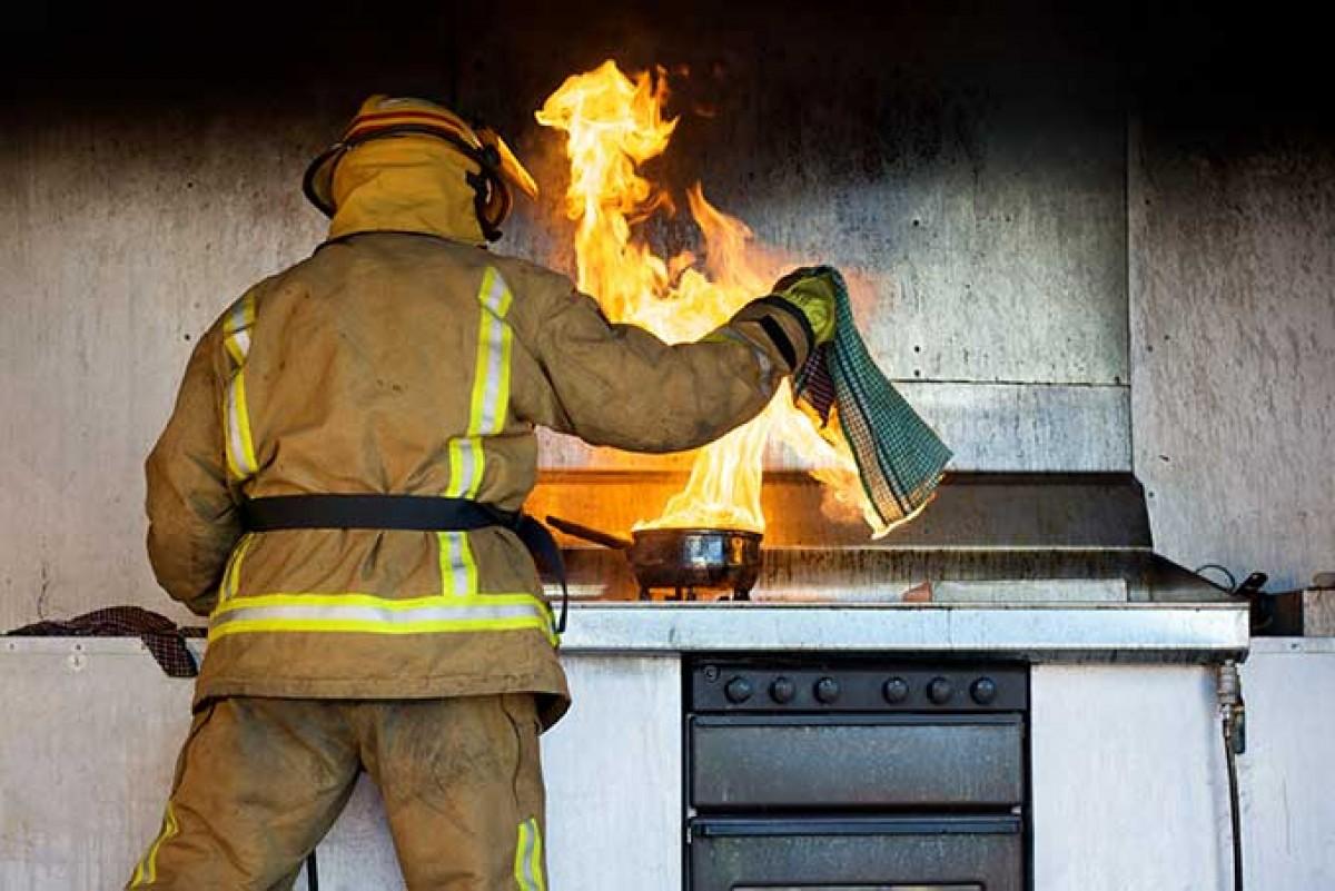 Un bomber, apagant el foc en una cuina