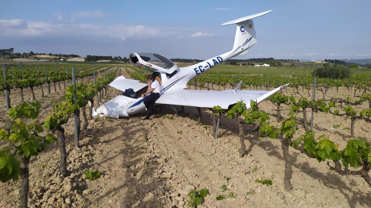 El pilot, parlant per telèfon damunt d'una ala de l'avioneta