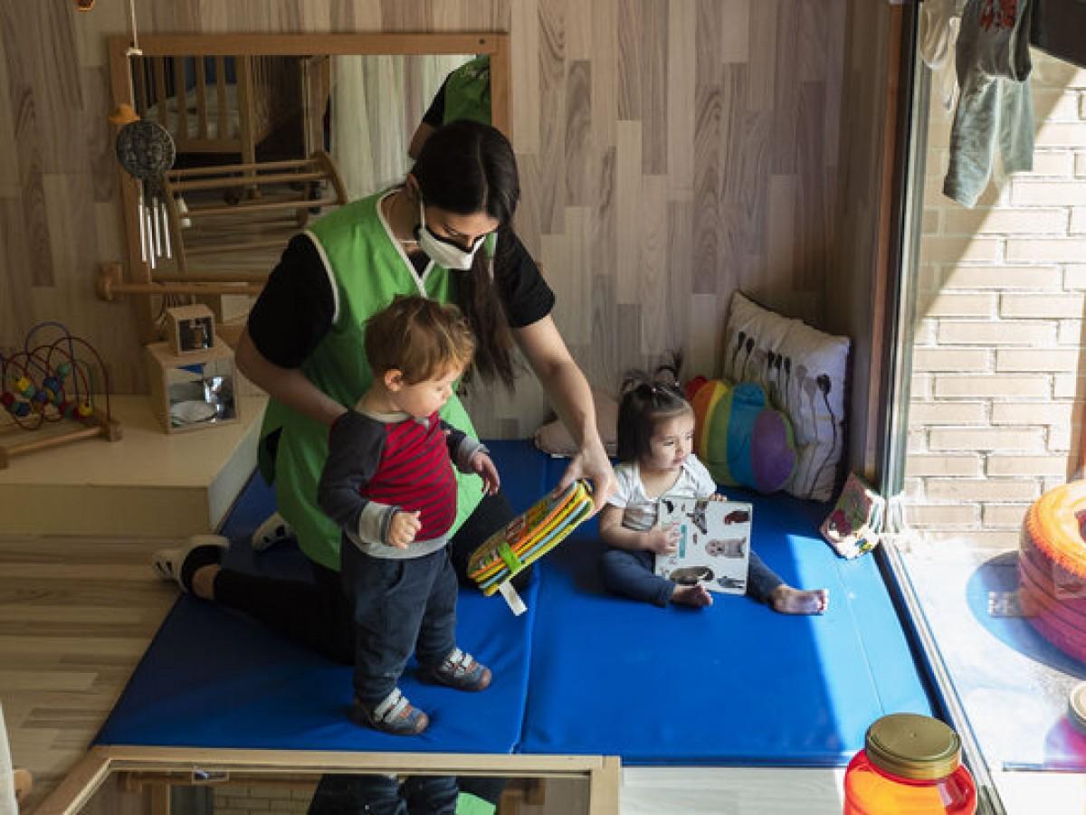 Una professora amb dos nadons a una escola bressol