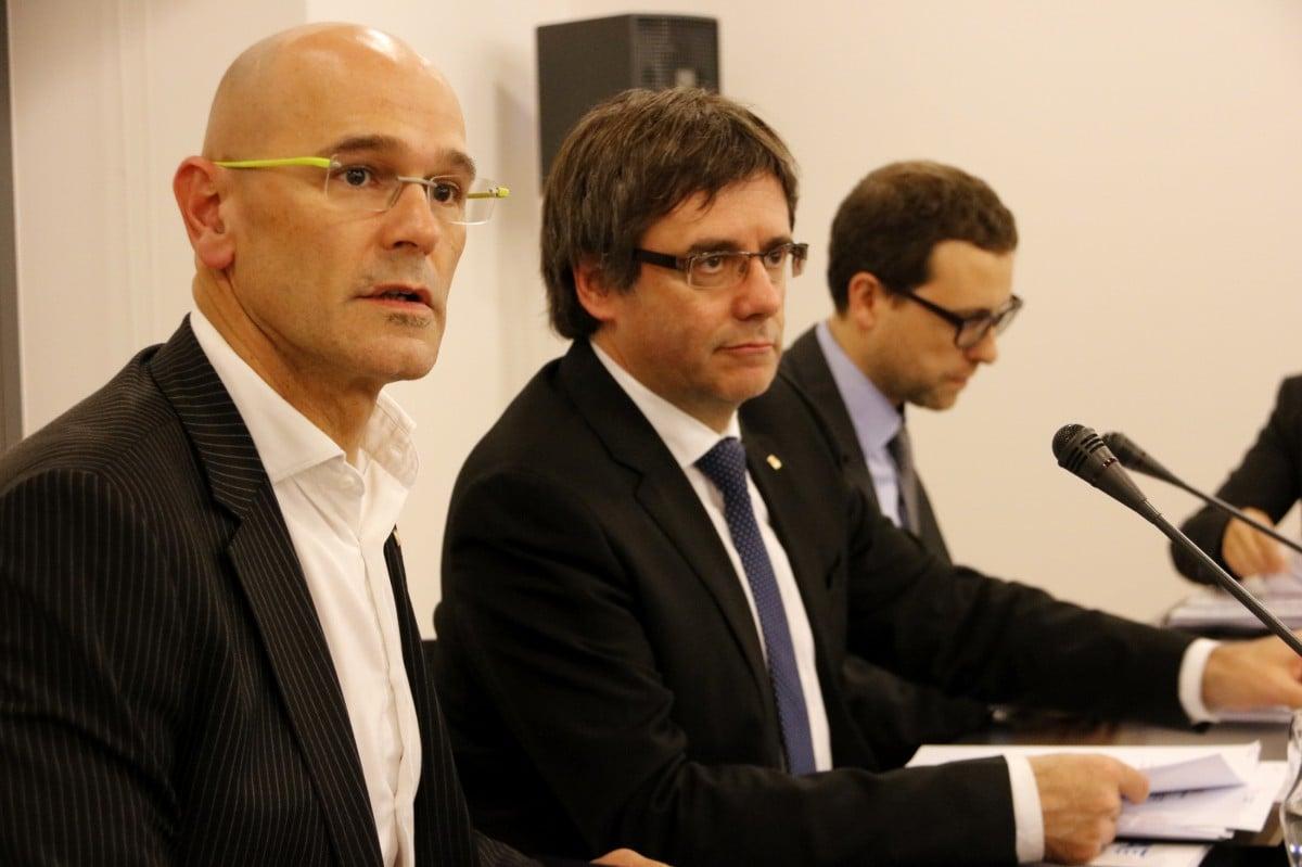Carles Puigdemont, acompanyat de Raül Romeva i Albert Royo, dos dels investigats en la causa contra l'acció exterior de la Generalitat