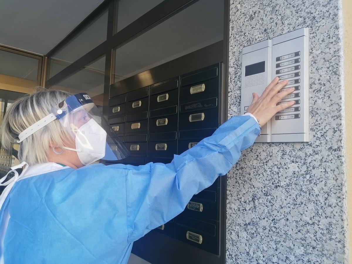 Una de les auxiliars del CAP del barri toca un timbre, al carrer de Romania de Can Parellada.
