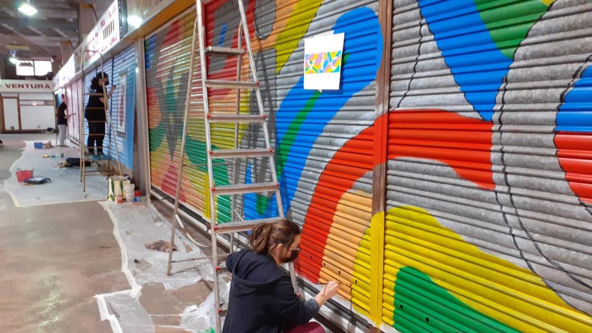 Alumnes de l'Escola d'Art d'Olot pinten les persianes del Mercat Municipal de Vic.