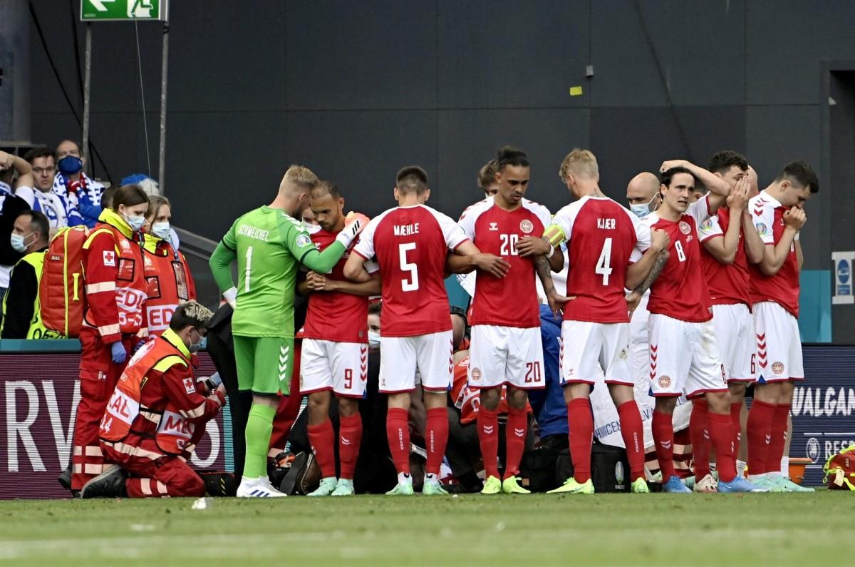 Els jugadors de Dinamarca, al voltant del seu company estirat al terra