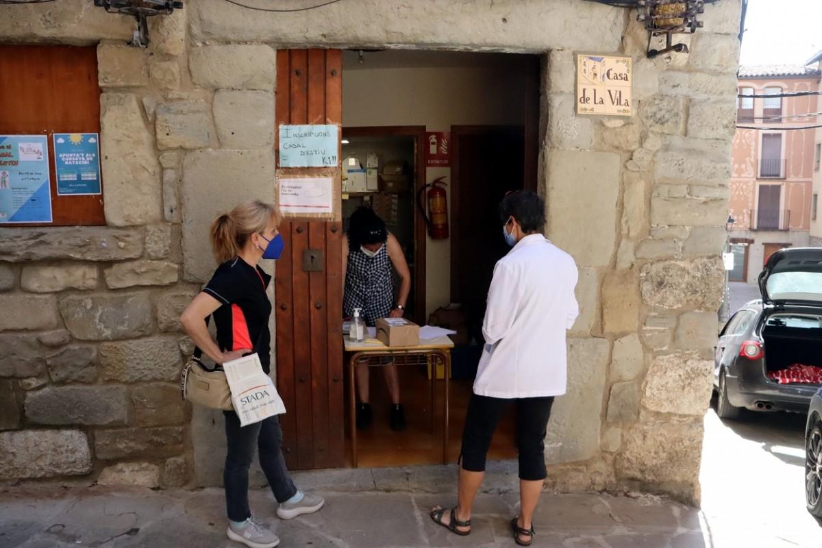 Dues persones esperen a l'exterior de l'oficina de Correus de Sant Llorenç de Morunys
