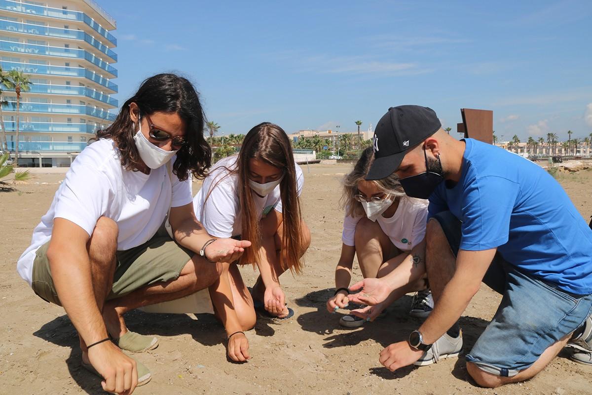 Un grup de membres de l'entitat Good Karma Projects recullen pellets a la platja de la Pineda.