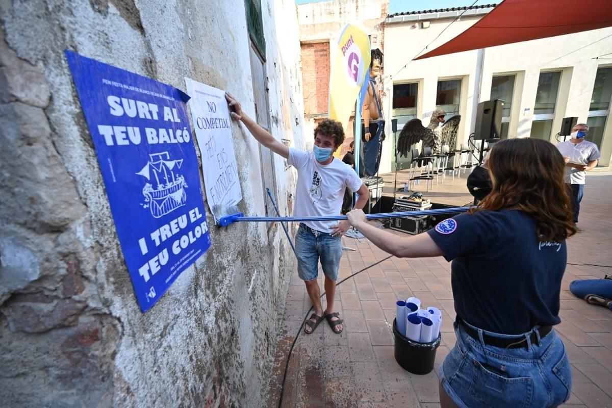 Responsables de les colles de Blancs i Blaus, enganxant cartells de la Festa Major a Roca Umbert