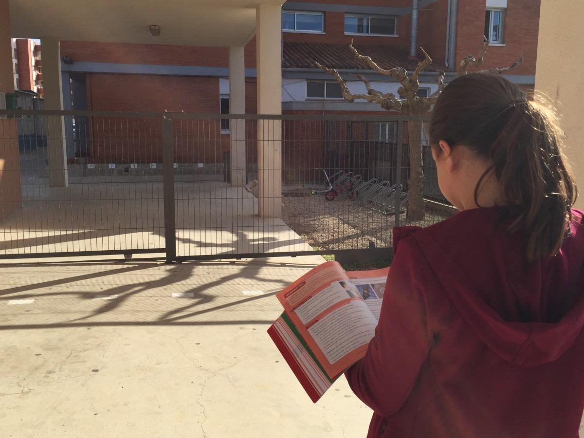Una nena es mira un llibre de text, al pati de l'escola