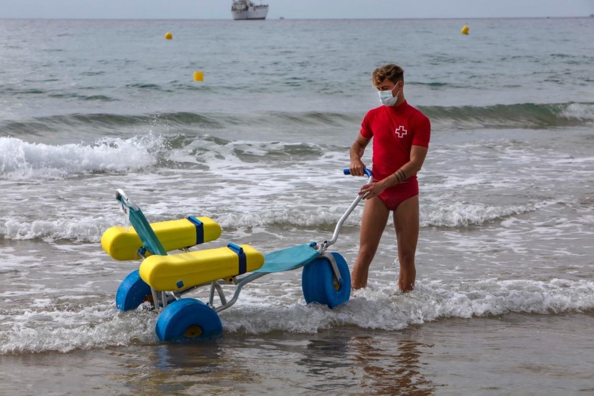 Un socorrista amb la cadira amfíbia per a infants que es pot usar a la platja de l'Arrabassada