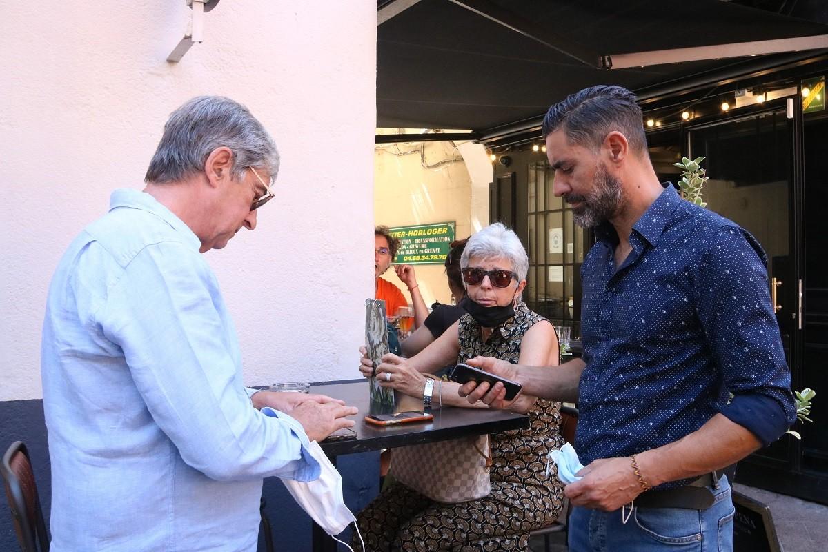 Un client mostra el passaport Covid a l'entrada d'un restaurant a Perpinyà