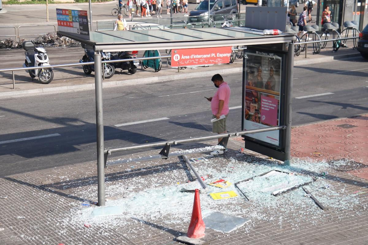Marquesina d'autobus trencada i motos cremades al fons, a Plaça Espanya