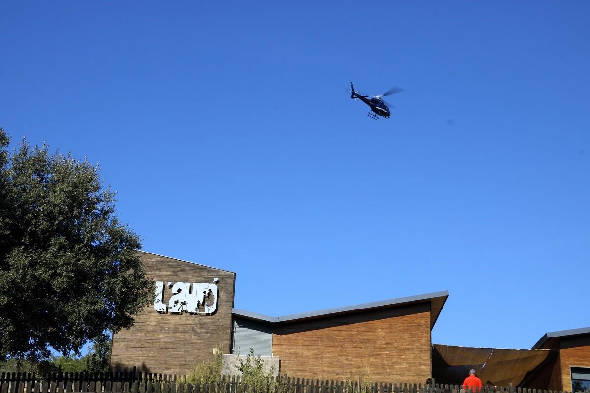 Pla mitjà on es pot veure un helicòpter dels Mossos sobrevolant la casa de colònies on s'ha perdut un menor al nucli de Llanera