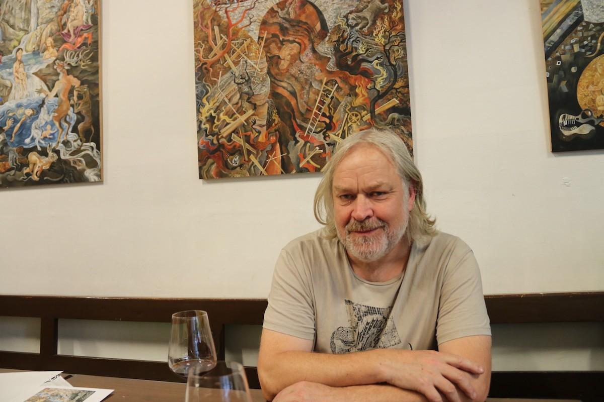 El pintor Peter Alan Hull davant de tres obres seves