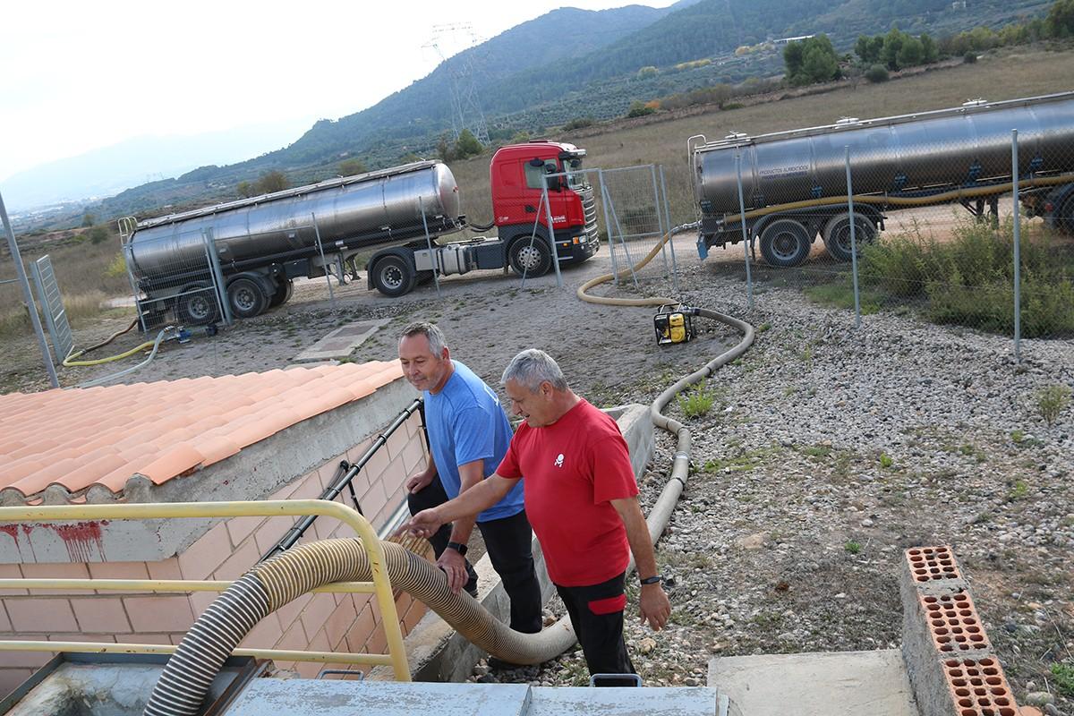 Uns operaris traspassant aigua dels camions cisterna al dipòsit de l'Espluga de Francolí.