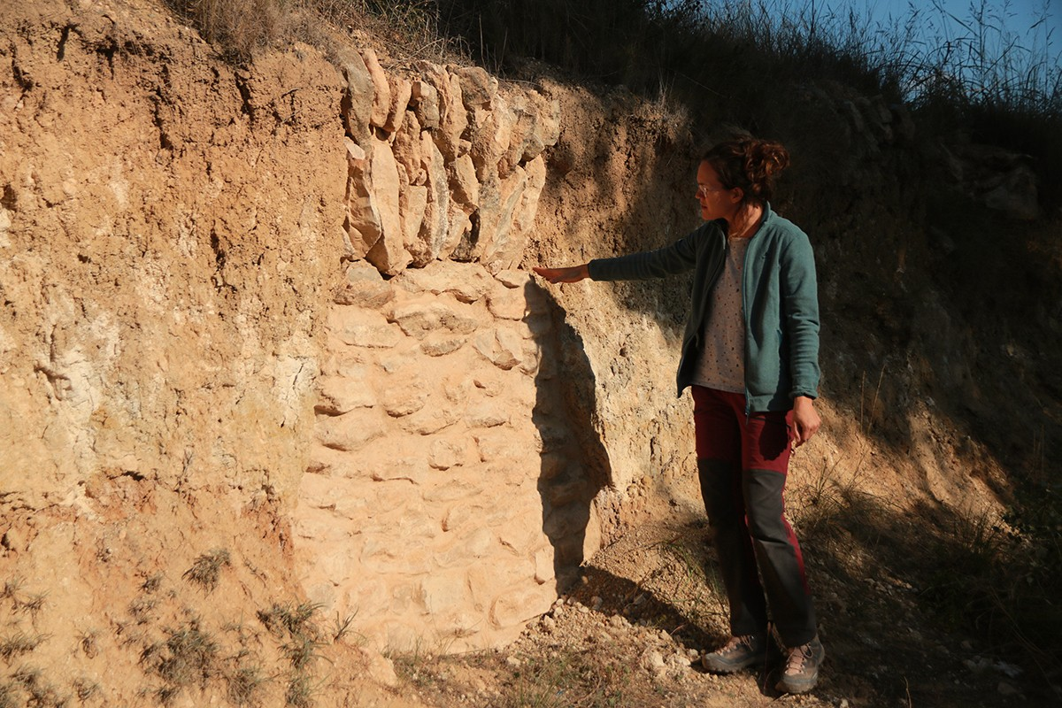 L'arqueòloga Georgina Prats mostrant la primera sitja descoberta per sorpresa l'any 2019, a Nulles.