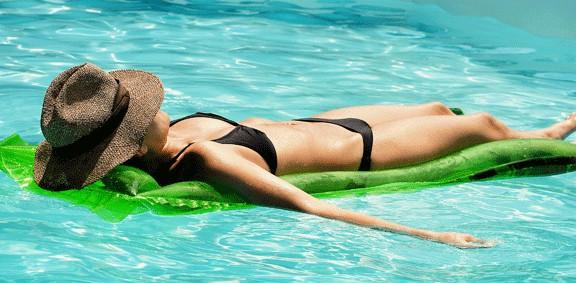 Una dona prenent el sol a la piscina